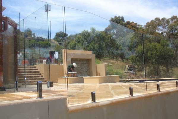 Frameless fencing on a retaining wall